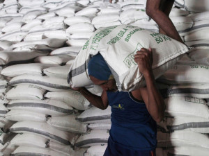 Workers load sacks of sugar from a warehouse onto a truck for distribution to the traders in Sidoarjo of Indonesia's East Java province